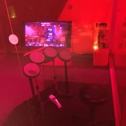 Friends can play Rock Band together inside a Plexi cube.